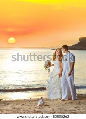 Bride and groom walking on the beach at sunrise - stock photo