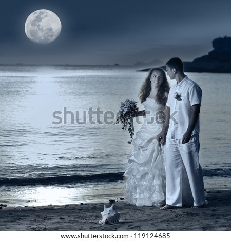Bride and groom walking on the beach under the moon