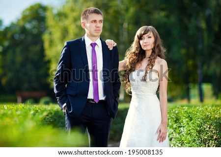 Bride and groom walking on the park