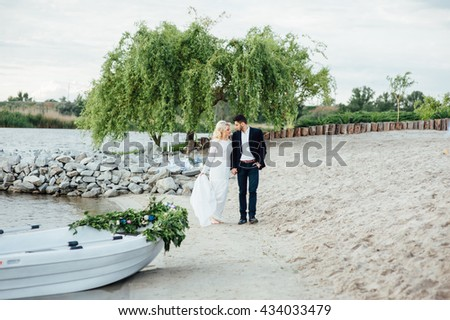 Bride and groom walking on the river, smiling and kissing