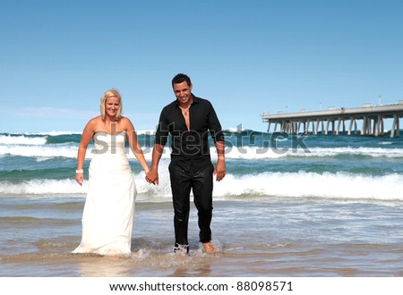 Bride and groom walking out of the ocean hand in hand.