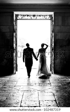 Bride and Groom walking through large doorway