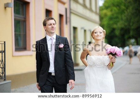 Bride and groom walking together - stock photo