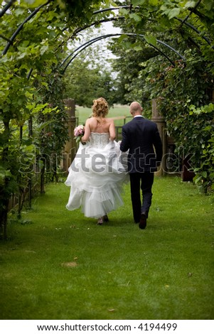 Bride and groom walking together in the garden