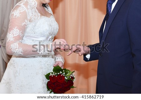 bride and groom wear wedding rings to each other - stock photo