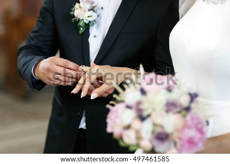 bride and groom wearing rings on the wedding ceremony