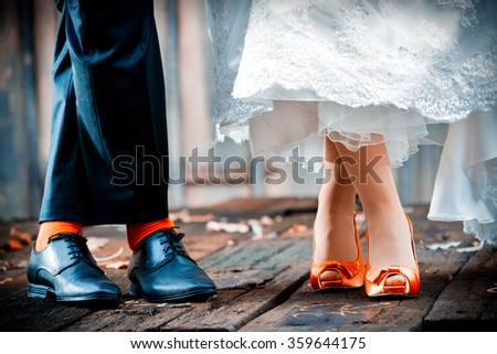 Bride and groom wearing stylish shoes matching colors - stock photo