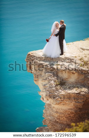 Bride and groom wedding at sea, newlywed couple embracing outdoors. Nam and woman ant marriage ceremony outdoor at ocean rocks. - stock photo