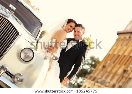 Bride and groom with a white retro car - stock photo