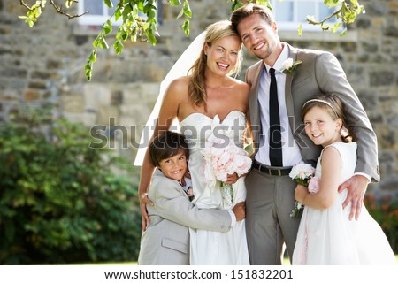 Bride And Groom With Bridesmaid And Page Boy At Wedding - stock photo