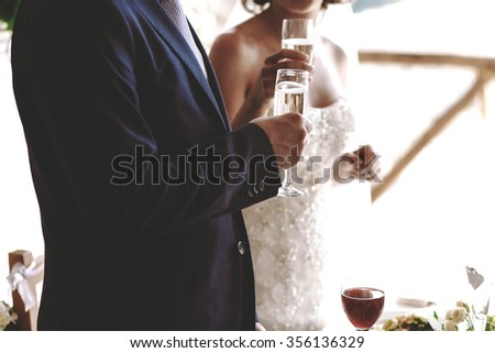 Bride and groom with glasses of champagne celebrating their wedding day. Hands of a man and a woman with a glass of white wine or champagne - stock photo
