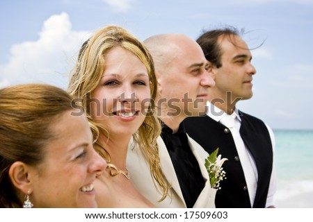 Bride and groom with groomsmen and bridesmaid on the beach. Bride looking at camera