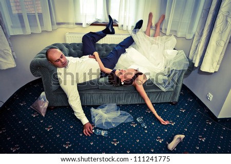 Bride and groom with hangover on the sofa - stock photo