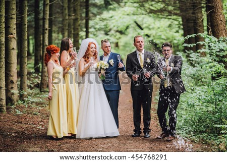 Bride and groom with happy groomsmen and bridesmaids having fun and popping champagne, luxury wedding celebration, hilarious moment. Newlyweds fun with friends. Bride with red hair color. Funny day