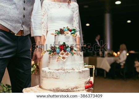bride and groom with rustic wedding cake on wedding banquet with red rose and other flowers