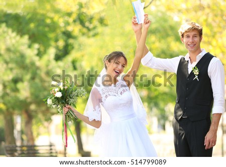 Bride and groom with tickets in park