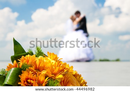 bride and groom with wedding flowers - stock photo