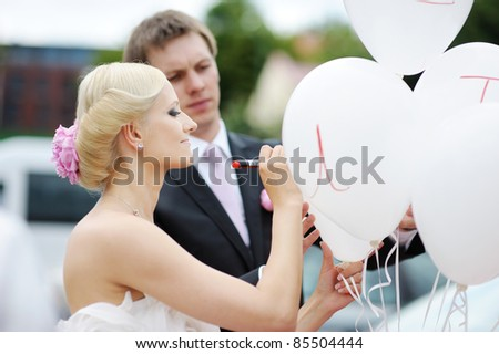 Bride and groom writing on a balloon - stock photo
