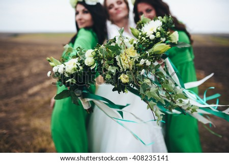 Bride and her bridesmaids with their bouquets - stock photo