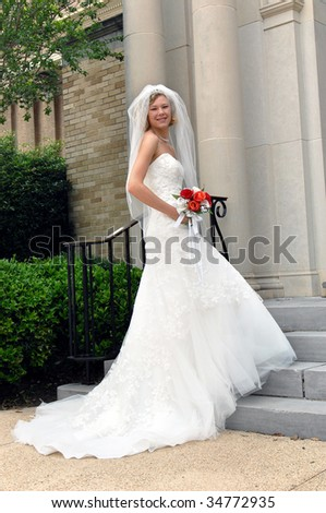 Bride anxiously begins her steps into the church.  She is smiling happily as she begins her big day.  She is holding a bouquet of red and orange silk roses. - stock photo