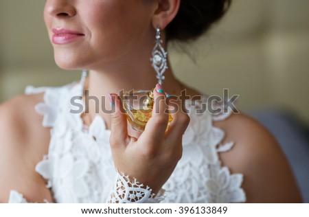 bride applying perfume. Bride spraying perfume on her neck - stock photo