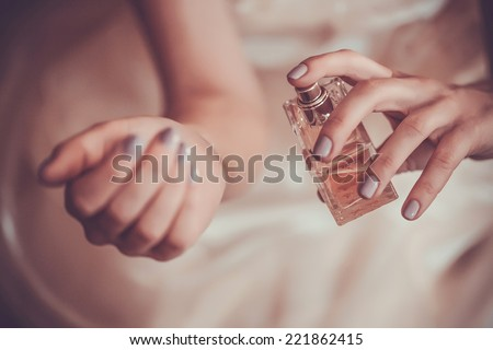 bride applying perfume on her wrist - stock photo