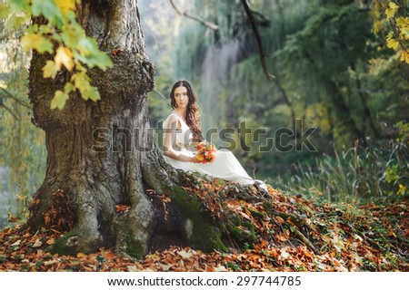 Bride at countryside next to old big tree. Wedding in forest.