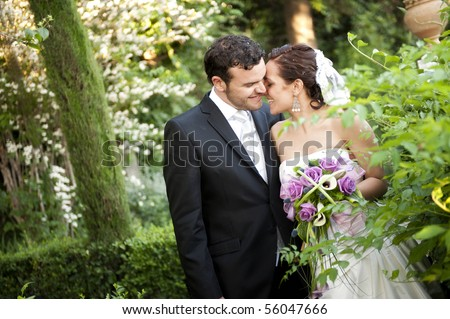 Bride at groom in green outdoors - stock photo
