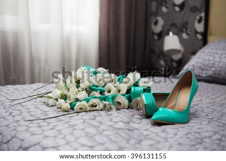 Bride attributes. Morning of the bride. Wedding bouquet of white roses and blue ribbons and blue patent leather high-heeled shoes. Preparations for the wedding ceremony - stock photo