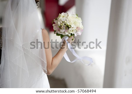 bride back with rose bouquet in hand on wind
