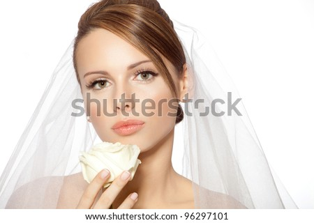 Bride beauty close up / Beautiful young brunette woman in a wedding dress with veil holding white rose - stock photo