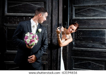 Bride behind the big old wooden gate calling the groom holding the flowers - stock photo