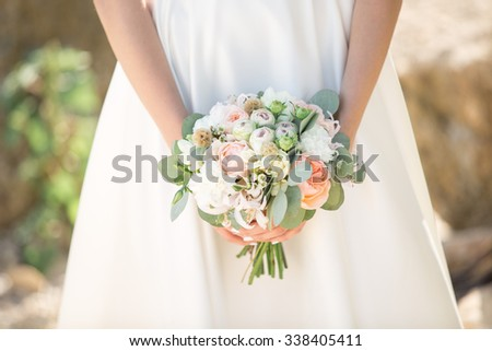 Bride boho style. Those girls are not seen are only visible hand with a bouquet and a long white dress. Bouquet of peach roses. The girl flowing white dress, photographed in nature.