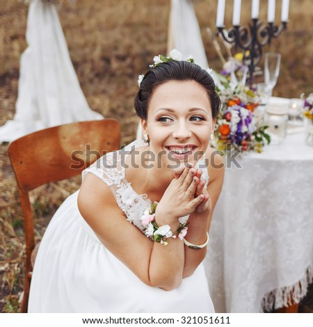 Bride burst of laughing, sitting near wedding decorations on table.  - stock photo