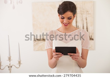 Bride chooses a wedding dress and using tablet computer - stock photo