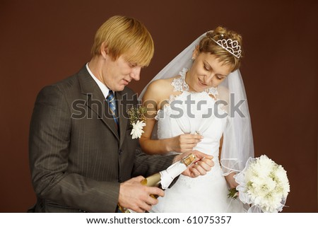 Bride couple opens a bottle of sparkling wine on brown background - stock photo