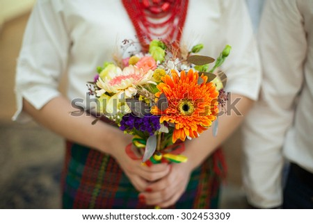 bride dressed in national dress holding a beautiful wedding bouquet