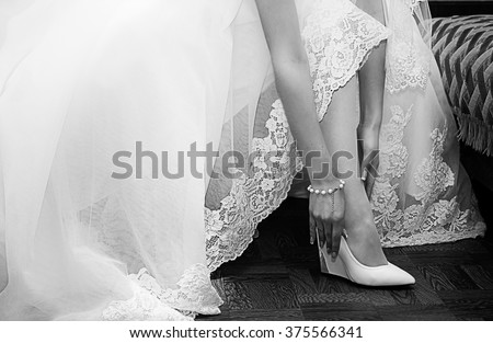 Bride dresses shoes before the wedding ceremony. Black and white photography - stock photo