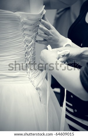Bride dressing the wedding dress - stock photo
