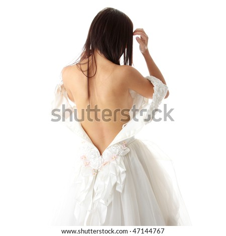 Bride dressing up her wedding dress on nude body, isolated - stock photo