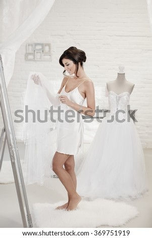 Bride dressing up on wedding-day, looking at veil. - stock photo