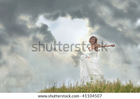Bride embraces and dances with the elements as she stands on a grassy hill. - stock photo