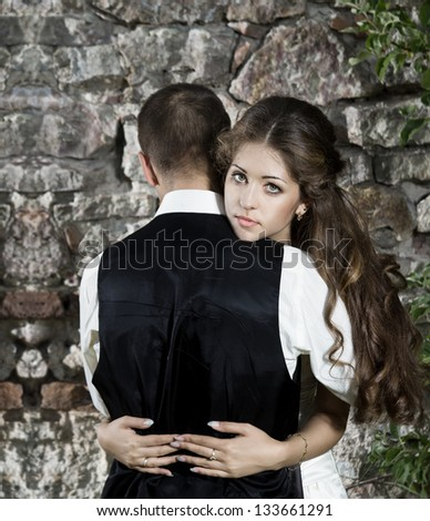 Bride embracing groom over groom stone brick wall outdoors