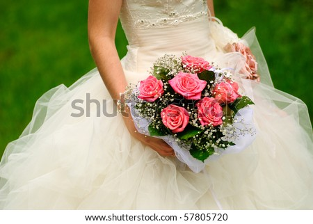 Bride from behind throw the bouquet from pink roses on old wall background
