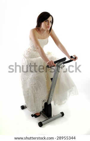 Bride getting in shape by working-out on a gym bike - stock photo