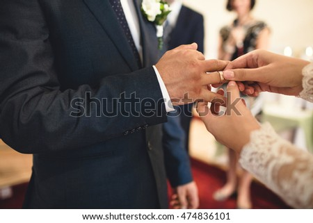 bride  gives her  young  groom  a gold ring