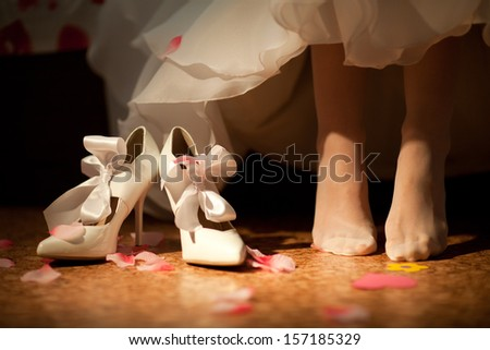 bride going to put on shoes - stock photo