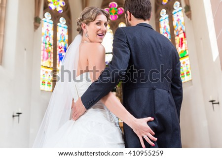 Bride grabbing ass of groom at wedding in church - stock photo