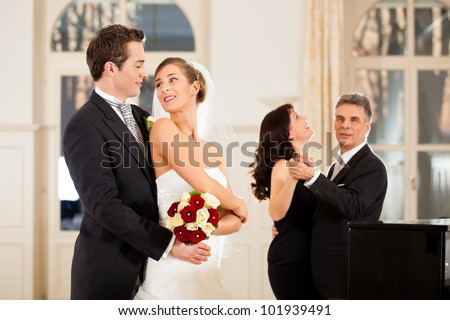 Bride, groom and wedding guests dancing waltz on the wedding day - stock photo