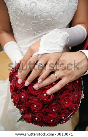 Bride & groom hands over wedding dress - stock photo